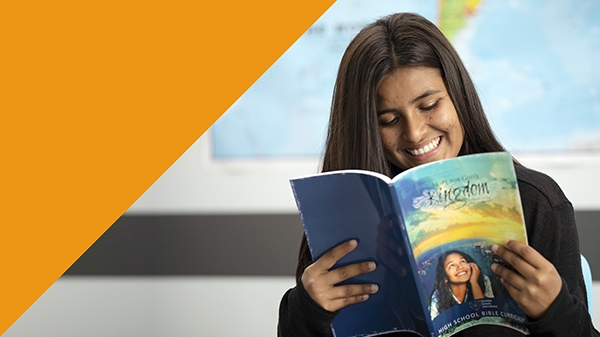 "High school student reading ""Hope for God's Kingdom"" textbook"